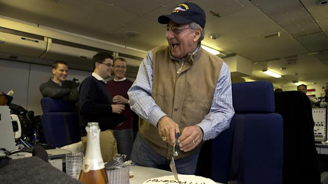 "The traveling staff on board the E-4B surprise U.S. Defense Secretary Leon Panetta with a cake that says ""arrivederci,"" in a celebration in honor of the last leg of his final overseas trip as secretary, en route to Washington on Saturday, Jan. 19, 2013. The plastic meat axe at right was a joke gift from the staff, at the secretary's reference to budget sequestration being a meat axe. (AP Photo/Jacquelyn Martin)"