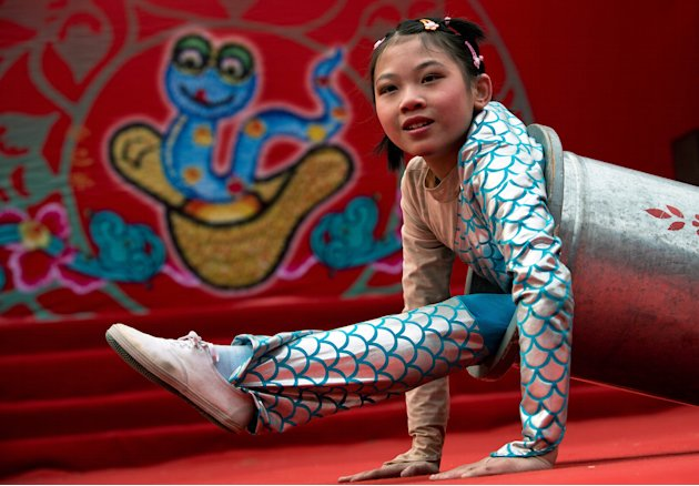 A Chinese girl uses a cylinder while performing an acrobatic show at the Dongyue Temple fair during the second day of the Chinese New Year in Beijing Monday, Feb. 11, 2013. Thousands attended temple f