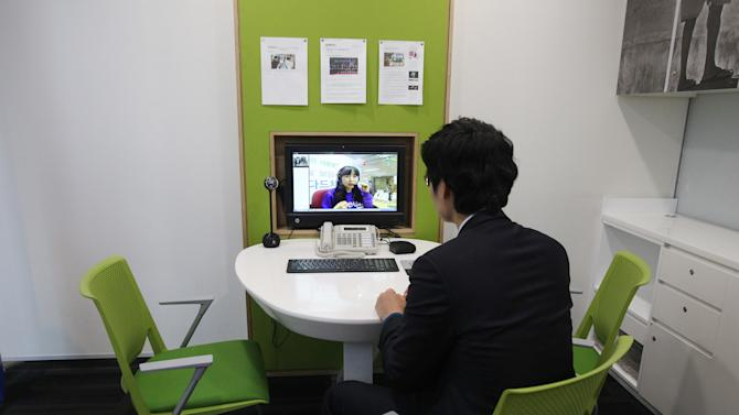 """In this Friday, Jan. 11, 2013 photo, customer Chung Yong-min does banking through a screen monitor connected to a video conference with bank employee Oh Ji-young, located in another office, at a Smart Banking Center in Seoul, South Korea. Standard Chartered is expanding its """"smart banking'' branches that employ a staff of three instead of eight. The company expects to have 30 more by the end of 2013. (AP Photo/Ahn Young-joon)"""