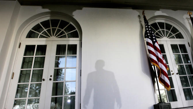 FILE - In this Tuesday, Oct. 13, 2009 file photo, the shadow of President Barack Obama is cast on a wall as he leaves a news conference in the Rose Garden of the White House in Washington after the Senate Finance Committee voted to approve a health care bill. (AP Photo/Pablo Martinez Monsivais)