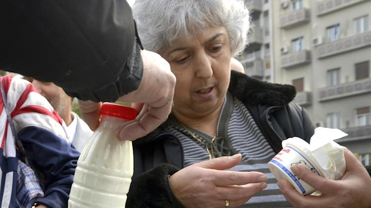 A woman receives dairy products given by cattle farmers  in the city center of Thessaloniki, northern Greece, on Tuesday, Dec. 13, 2011. The farmers were protesting at low market prices for their products.  (AP Photo/Nikolas Giakoumidis)