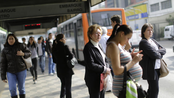 People wait for the bus at a bus stop in Sao Paulo, Brazil, Thursday, June 20, 2013. Leaders in Brazil's two biggest cities said Wednesday that they reversed an increase in bus and subway fares that ignited anti-government protests that have spread across the nation in the past week. (AP Photo/Nelson Antoine)