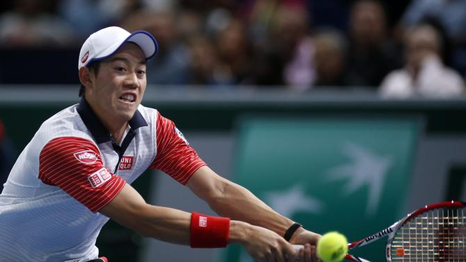 Nishikori of Japan returns a shot during his men's singles tennis match against Tsonga of France in the third round of the Paris Masters tennis tournament at the Bercy sports hall in Paris
