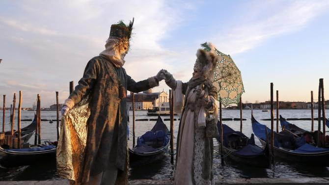 Masked revellers pose in front of St. Mark's square during the first day of carnival, in Venice
