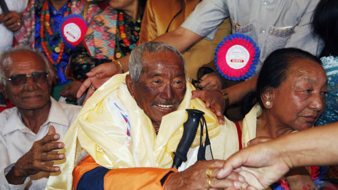 FILE - In this May 31, 2008 file photo, Min Bahadur Sherchan, center, who became the oldest person to climb Mount Everest on May 25, 2008 shakes hands on his arrival in Katmandu, Nepal. Yuichiro Miura, an 80-year-old Japanese extreme skier who just missed becoming the oldest man to reach the summit of Mount Everest five years ago is back on the mountain to make another attempt at the title. Unfortunately for Miura, Sherchan, the slightly older man who nabbed the record a day before he could in 2008 is fast on his heels. (AP Photo/Binod Joshi, File)