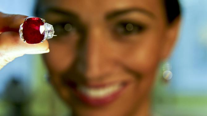 """A model holds the """"Sunrise Ruby"""" during an auction preview at Sotheby's auction house in Geneva"""