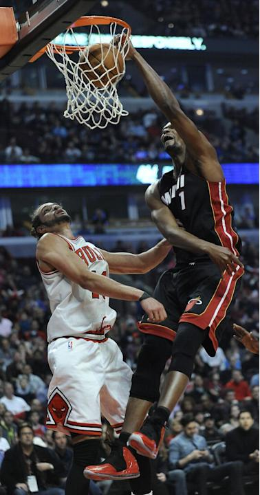 Miami Heat's Chris Bosh (1) dunks over Chicago Bulls Joakim Noah during the first quarter of an NBA basketball game in Chicago, Sunday, March 9, 2014