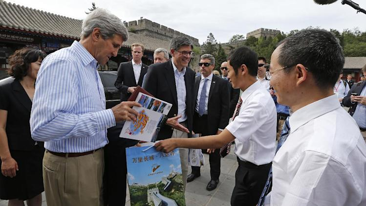 U.S. Secretary of State John Kerry, left, and Treasury Secretary Jack Lew, center, get certificates saying that they have climbed to the top of the Great Wall as well as photo books about the wall from Guo Jiaqiang, second right, deputy director of the Badaling Foreign Affairs Office, and with Chen Fei, right, deputy director of the Badaling Great Wall Special District, while touring the Badaling section of the Great Wall of China in Beijing Tuesday, July 8, 2014. Kerry and Lew are in Beijing to attend the annual U.S.-China Strategic and Economic Dialogue. (AP Photo/Jim Bourg, Pool)