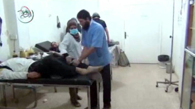 This Monday, Aug. 26, 2013 image taken from amateur video footage provided by the Media Office Of Moadamiyeh purports to show medics assisting a man lying on a bed who appears to be shaking uncontrollably as a UN inspection team visits a makeshift hospital in Moadamiyeh, a suburb of the Syrian capital of Damascus. Doctors Without Borders said 355 people were killed in an artillery barrage by regime forces on Wednesday, Aug. 21, 2013 that included the use of toxic gas. The media office of Moadamiyeh is a loosely organized Anti-Assad activist group based in Moadamieyh which posts video and still images of violence and other developments from the region. (AP Photo/Media Office Of Moadamiyeh)