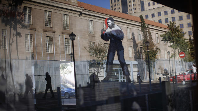 A giant statue of former South African President Nelson Mandela stands outside the Magistrate's Court, in Johannesburg, South Africa, Tuesday, June 18, 2013. The statue is the work of Marco Cianfanelli. Well-wishers continued to send messages of love and support to Nelson Mandela, as he remained in hospital in a serious condition with a lung infection. (AP Photo/Jerome Delay)