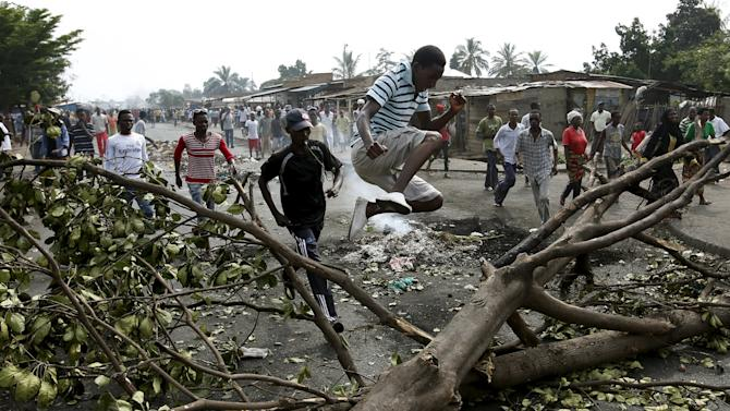 A protester jumps over a barricade during a protest against President Pierre Nkurunziza and his bid for a third term in Bujumbura