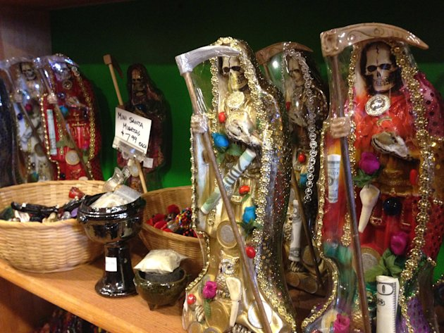 in this Feb. 13, 2013 photo, statues of La Santa Muerte are shown at the Masks y Mas art store in Albuquerque, N.M. La Santa Muerte, an underworld saint most recently associated with the violent drug