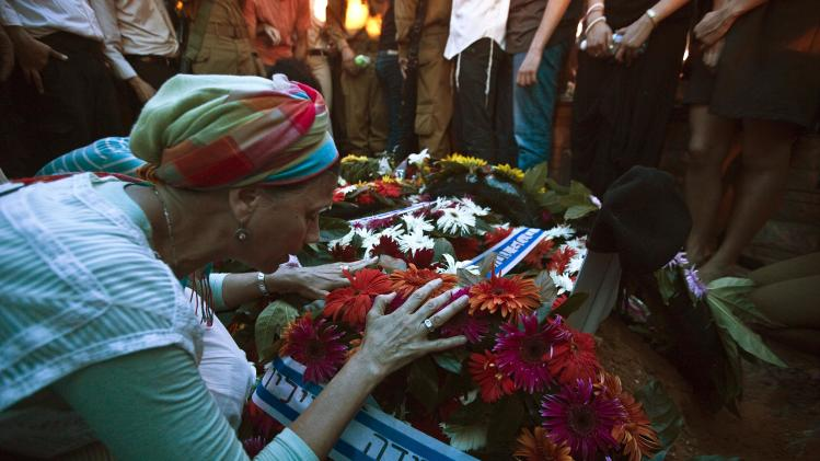 A mourner touches a wreath placed on grave of fallen Israeli soldier in Modi'in