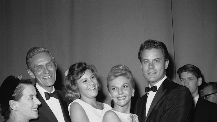 """FILE - In this Oct. 17, 1963 file photo, Broadway star Mary Martin is congratulated backstage after the opening of her new musical """"Jennie"""" at New York's Majestic Theater. From left are Beatrice Lillie Richard Halliday, husband of Mary Martin, Heller Weir, daughter of Mary Martin, and Martin's son Larry Hagman.  Actor Larry Hagman, who for more than a decade played villainous patriarch JR Ewing in the TV soap Dallas, has died at the age of 81, his family said Saturday Nov. 24, 2012. (AP Photo/Ray Howard, File)"""