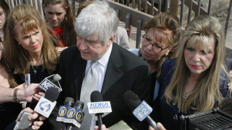FILE - In this April 7, 2010 file photo, former Pennsylvania state Sen. Jane Orie, left, her sisters Janine Orie, right, and Pennsylvania Supreme Court Justice Joan Orie Melvin, center right, listen as their brother Jack Orie, center, reads a statement to the press outside a magistrate's office in Pittsburgh. With the conviction of Melvin and Janine Orie on Thursday, Feb. 21, 2013, and Jane Orie's 2012 conviction, all three sisters were found guilty in campaign related in campaign corruption crimes. (AP Photo/Keith Srakocic, File)