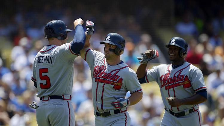 Atlanta Braves' Dan Uggla, center, is congratulated by teammates Freddie Freeman, left, and Justin Upton after hitting a three-run home run during the third inning of a baseball game against the Atlanta Braves, Sunday, June 9, 2013, in Los Angeles. (AP Photo/Mark J. Terrill)