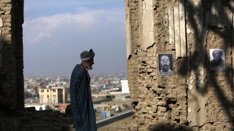 A man looks at pictures of victims of the three-decade war during a Social Association of Afghan Justice Seekers (SAAJS) photo exhibition in Kabul