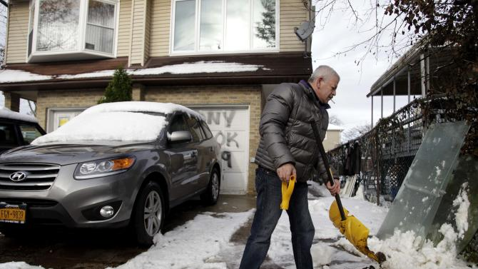 Gennady Naydis keeps clearing his driveway even as the handle breaks off his shovel in the New Dorp section of Staten Island, N.Y., Thursday, Nov. 8, 2012. The New York-New Jersey region woke up to a layer of wet snow and more power outages after a new storm pushed back efforts to recover from Superstorm Sandy. (AP Photo/Seth Wenig)