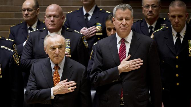 New York Police Commissioner Bratton and New York Mayor de Blasio hold their hands on their hearts as they take part in a New York Police Department Promotion Ceremony at Police Headquarters in the Manhattan borough of New York