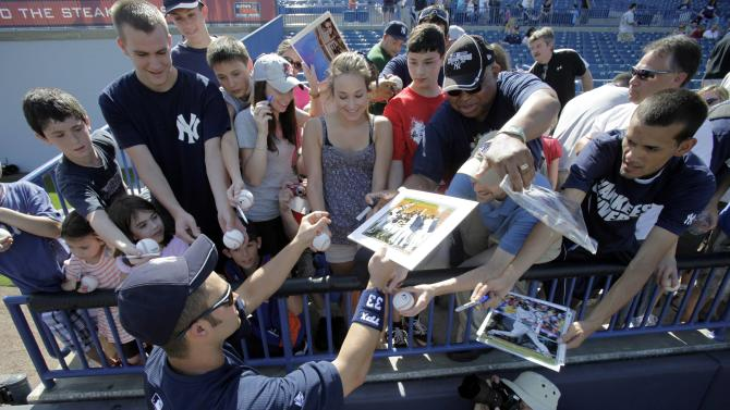 FILE-  This Wednesday, Feb. 23, 2011 file photo shows New York Yankees outfielder Nick Swisher as he signs autographs for fans during a baseball spring training workout at Steinbrenner Field in Tampa, Fla.  Fans have been traveling to Central and South Florida for decades to get a glimpse of veteran stars and new prospects alike during spring training.    (AP Photo/Charlie Neibergall, FILE)