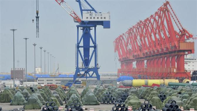 File photo of a worker riding his bicycle past piles of steel coils for export at a port in Yingkou