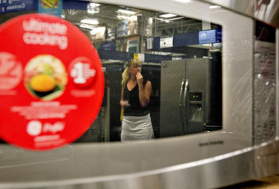 In this June 19, 2012,photo, a shopper is reflected in a microwave oven on display on a showroom floor at Lowe's store in Atlanta.  Consumer confidence fell in June for the fourth month in a row as lingering worries about the economy outweighed relief at the gas pump, according to a private research group. (AP Photo/David Goldman)