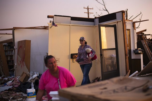 Woman carries a stuffed animal and flag out of a home as she helps a family friend salvage items from her uncle's home after it was almost destroyed by a tornado in Moore, Oklahoma