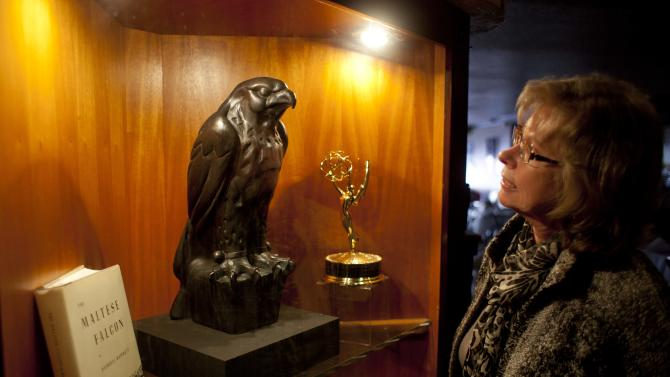 "In this photo taken Thursday, Sept. 27, 2012, Gloria Para of San Francisco, looks at a replica of the Maltese Falcon at John's Grill in San Francisco. San Francisco has a long history as a favorite site for filmmakers and the movie buffs who want to see the spots where their favorite scenes took place, from Fort Point under the Golden Gate Bridge where Jimmy Stewart saved Kim Novak in ""Vertigo"" to the steps of City Hall, where Sean Penn gave an impassioned speech in ""Milk,"" to Alcatraz, stage for Clint Eastwood and many others. One of the city's oldest restaurants, the grill was a setting in author Dashiell Hammett's ""The Maltese Falcon."" The interior looks just as you would picture it from the book, filled with original period furnishings. The walls are covered with photos of famous customers and the second floor has a replica of the falcon, along with movie stills and foreign translations of the novel. (AP Photo/Eric Risberg)"