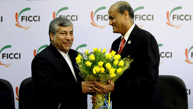 Federation of Indian Chambers of Commerce and Industry President, R. V. Kanoria, right, greets Iranian Energy Minister Majid Namjoo with a bouquet of flowers before an interactive business meeting with FICCI members in New Delhi, India, Wednesday, Oct. 10, 2012. (AP Photo/Altaf Qadri)