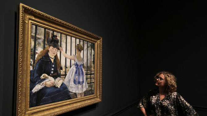 A Royal Academy of Arts employee poses for photographers in front of Manet's oil on canvas painting entitled 'The Railway, 1873' at the gallery in central London, Tuesday, Jan. 22, 2013. The painting depicts one of Manet's favourite models, Victorine Meurent, posing with a young girl in front of the railings of Gare Saint-Lazare, in Paris and is the first time this painting has been on display in London. The Royal Academy's major exhibition 'Manet: Portraying Life', that will run from Jan. 26 to April, 14, 2013, features over 50 paintings spanning the career of the modern artist. (AP Photo/Lefteris Pitarakis)