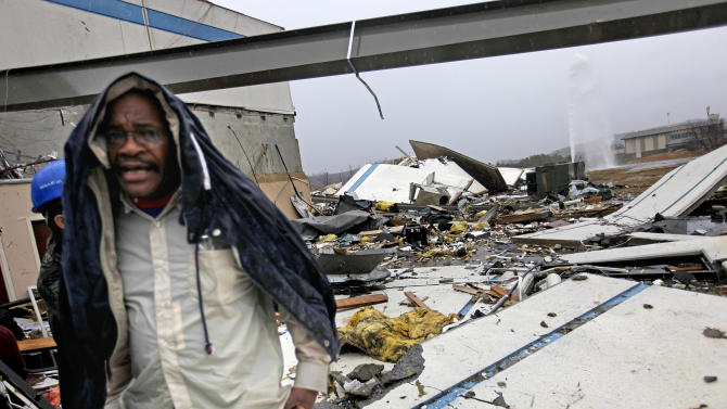 Workers look for personal belongings following a tornado at the Daiki plant, a metal fabrication company, Wednesday, Jan. 30, 2013, in Adairsville, Ga. A fierce storm system that roared across Georgia has left at least one person dead after it demolished buildings and flipped vehicles on Interstate 75 northwest of Atlanta. (AP Photo/David Goldman)