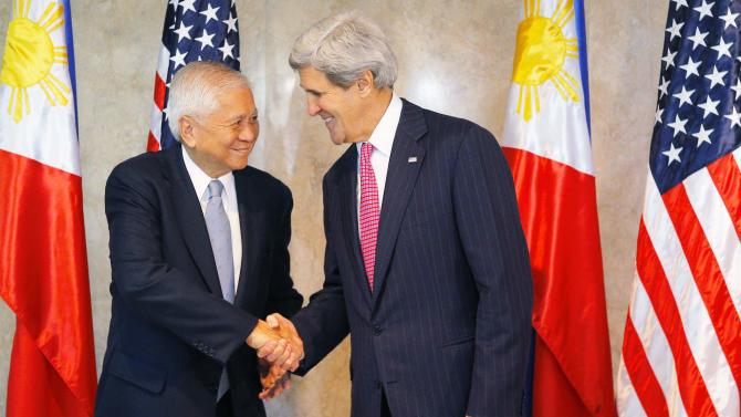 U.S. Secretary of State John Kerry is greeted by Philippines' Foreign Secretary Albert del Rosario for a meeting in Manila
