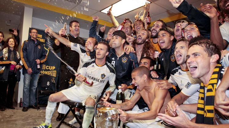 Los Angeles Galaxy midfielder David Beckham, bottom left, celebrates with his teammates after the Galaxy defeated the Houston Dynamo in the MLS Cup championship soccer match, Sunday, Nov. 20, 2011, in Carson, Calif. (AP Photo/Bret Hartman)