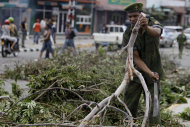A soldier removes tress that fell during the passing of Hurricane Sandy in Santiago de Cuba, Cuba, Friday Oct. 26, 2012. Sandy was a Category 2 hurricane when it wreaked havoc in Cuba on Thursday, killing 11 people in eastern Santiago and Guantanamo provinces as its winds and rain destroyed thousands of houses and ripped off roofs. (AP Photo/Franklin Reyes)