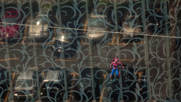 A Spider-Man model hangs from a glass facade of a spa building in Guangzhou, Guangdong province