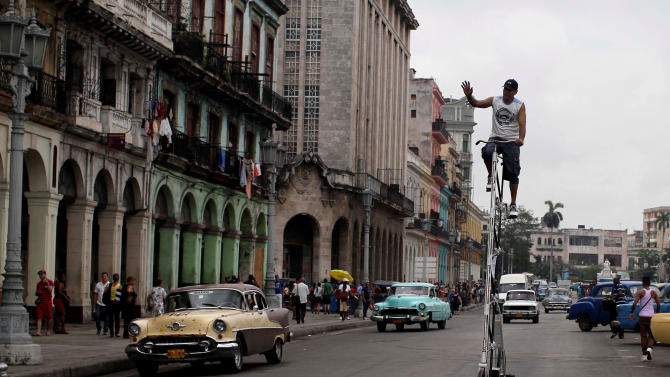FILE - In this May 18, 2012 file photo, Felix Guirola waves to people as he takes his self-made 3.45 meters (11 feet) tall bicycle for a spin through downtown Havana, Cuba. Guirola has been riding tall since 1983, when seeing a tandem bike inspired him to build up instead of out. He said his first tall bike measured 5.3 feet (1.6 meters), and they got progressively taller until five years later he was riding 18 feet (5.5 meters) in the air at Ciego de Avila carnivals. (AP Photo/Franklin Reyes, File)