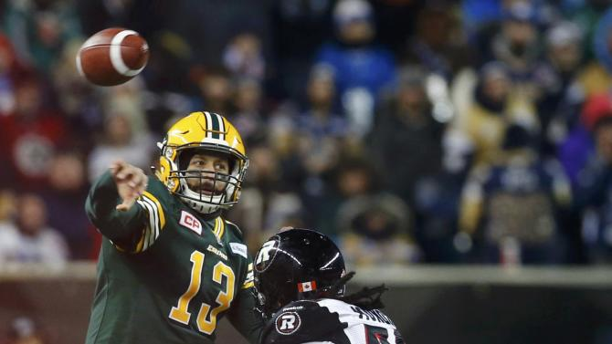 Edmonton Eskimos quarterback Reilly throws a pass under pressure from Ottawa Redblacks' Munoz during the third quarter of the CFL's 103rd Grey Cup championship football game in Winnipeg