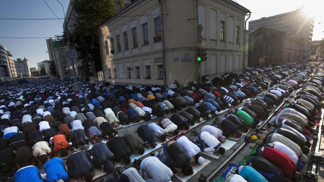 Muslim men, bowing toward Mecca, perform Eid al-Fitr prayers that marks the end of the holy fasting month of Ramadan in Moscow, Russia, Sunday, Aug. 19, 2012. More than two hundred thousand Muslims gathered at Moscow's mosques to celebrate the Eid al-Fitr. (AP Photo/Alexander Zemlianichenko Jr)