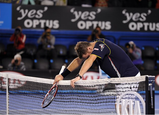 Switzerland's Stanislas Wawrinka rests on the net after losing his fourth round match against Serbia's Novak Djokovic at the Australian Open tennis championship in Melbourne, Australia, Sunday, Jan. 2