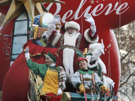 A float carrying Santa and his elves waves to spectators along 6th Ave during the 89th Macy's Thanksgiving Day Parade in the Manhattan borough of New York