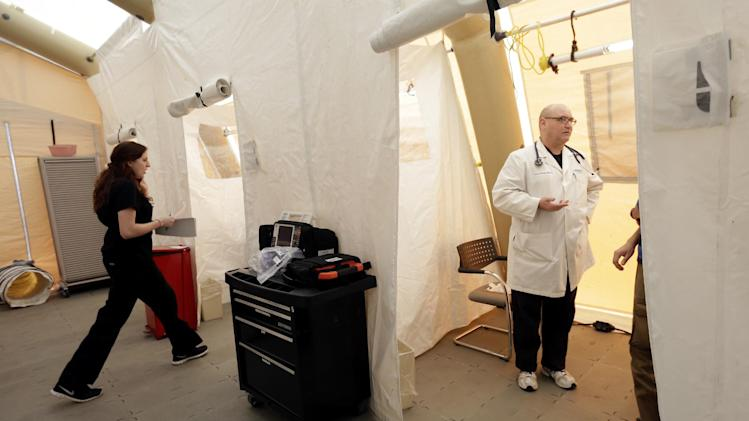 "Registered nurse Michelle Newbury, left, and physician assistant Scott Fillman meet with patients, not pictured, in a tent set up for a people with flu symptoms, just outside the emergency entrance at the Lehigh Valley Hospital Thursday, Jan. 10, 2013, in Allentown, Pa.  The Pennsylvania Department of Health designated flu as now ""widespread"" throughout the commonwealth. There have been more than 11,000 laboratory-confirmed flu cases in the state since the flu season began in mid-December. (AP Photo/Matt Rourke)"