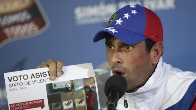 Opposition presidential candidate Henrique Capriles holds up a graphic and photograph as he says that an unusually high number of votes during Sunday's presidential election were made by voters who were assisted by an electoral worker, during a press conference at his campaign headquarters in Caracas, Venezuela, Tuesday, April 16, 2013.  Capriles called off the planned opposition march in Caracas Wednesday demanding a vote-by-vote recount of Sunday's presidential election after President-elect Nicolas Maduro summoned his supporters to take to the streets in the capital, raising the possibility of a confrontation with anti-government protesters. (AP Photo/Ramon Espinosa)