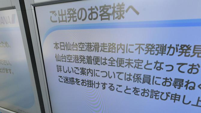 A bulletin board posts a notice that flights in and out of the airport are suspended after an unexploded bomb was found inside a runway, over the counter at Sendai Airport in Sendai, northern Japan Tuesday, Oct. 30, 2012. Local police official said flights in and out of the airport were canceled Tuesday after the 250-kilogram (550-pound) bomb was uncovered during construction near a runway. It was identified as American-made and is believed to be a dud from World War II. (AP Photo/Kyodo News) JAPAN OUT, MANDATORY CREDIT, NO LICENSING IN CHINA, FRANCE, HONG KONG, JAPAN AND SOUTH KOREA