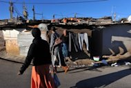 A woman dries her laundry in a street of the Alexandra township of Johannesburg. The ramshackle township that was Nelson Mandela's first home in Johannesburg sits across a highway from the gleaming high-rise buildings of Sandton
