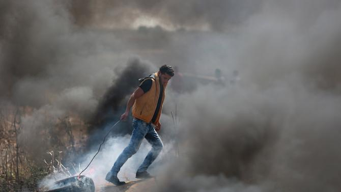 Palestinian protester pulls a burning tyre during clashes with Israeli troops near the Israeli border fence in the east of Gaza City