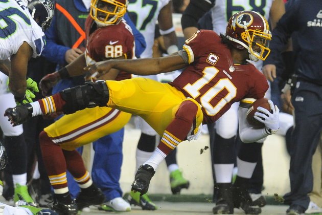 Washington Redskins quarterback Robert Griffin III flies through the air as he is knocked out of bounds during the first half of an NFL wild card playoff football game against the Washington Redskins
