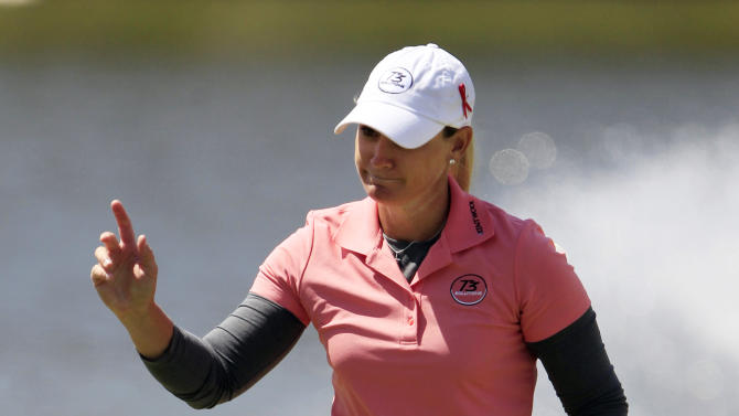 Kristy McPherson acknowledges the cheers of the fans after sinking a birdie putt on the 18th hole during the first round of the LPGA Tour North Texas Shootout golf tournament, Thursday, April 25, 2013, at Los Colinas Country Club in Irving, Texas. (AP Photo/John F. Rhodes)
