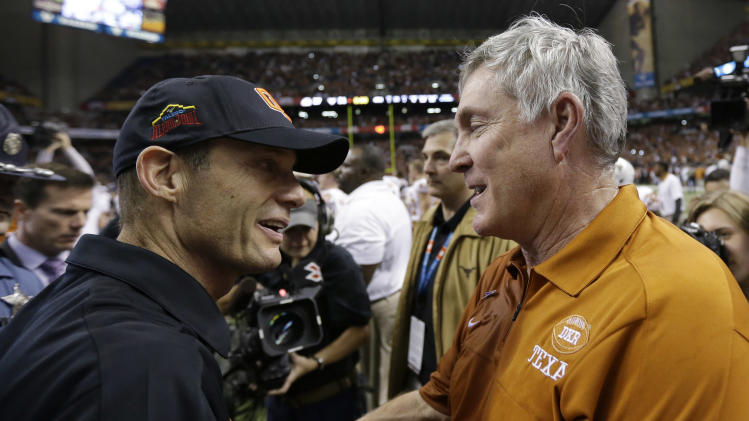 Oregon State head coach Mike Riley, left, and Texas head coach Mack Brown, right, meet at midfield following then Alamo Bowl NCAA football game, Saturday, Dec. 29, 2012, in San Antonio.  Texas won 31-27. (AP Photo/Eric Gay)