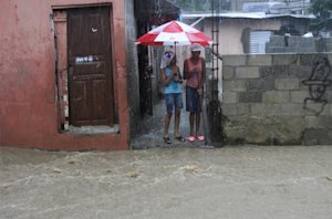 Women stand outside their home on a flooded street …
