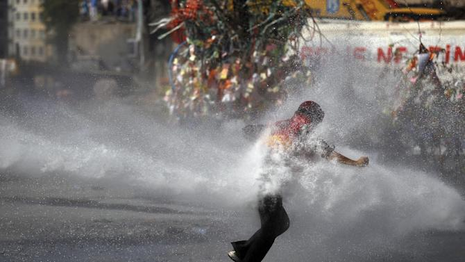 FILE - In this Tuesday, June 11, 2013, file photo, a protester tries to remain standing as a police water cannon fires water during clashes in Taksim square in Istanbul. Hundreds of police in riot gear forced through barricades in Istanbul's central Taksim Square early Tuesday, pushing many of the protesters who had occupied the square for more than a week into a nearby park. (AP Photo/Kostas Tsironis, File)